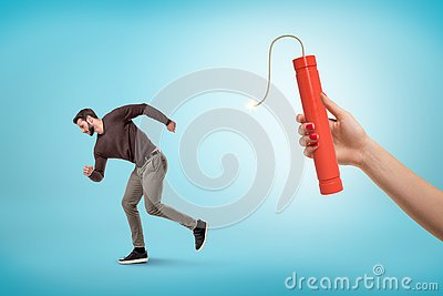 Side view of man in casual outfit running away from female`s hand holding lit dynamite stick.