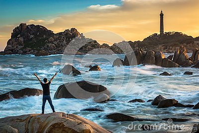 A Happy Man Celebrating Victory on The Top of A Big Rock by The Ocean