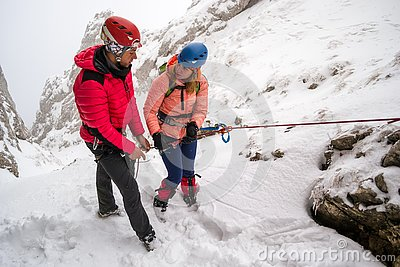 Two mountaineers discussing safety abseiling procedures before rappeling down a snowy chutte, on a difficult Winter route
