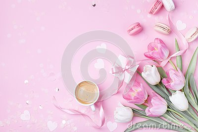 stock image of morning cup of coffee, cake macaron, gift box and spring tulip flowers on pink background. beautiful breakfast for women day