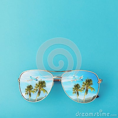 stock image of sunglasses with palm trees, a plane and mountains reflected in them. concept on the theme of vacation and travel with copy space