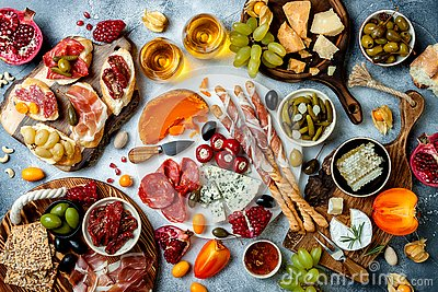 Appetizers table with antipasti snacks and wine in glasses. Bruschetta or authentic traditional spanish tapas set, cheese and meat
