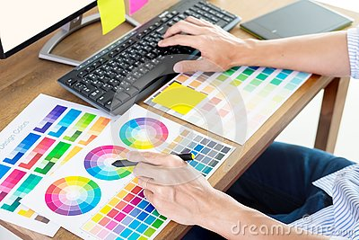 stock image of graphic designer or creative holding mouse and do his work material color pantone swatch samples art tools at desk in office