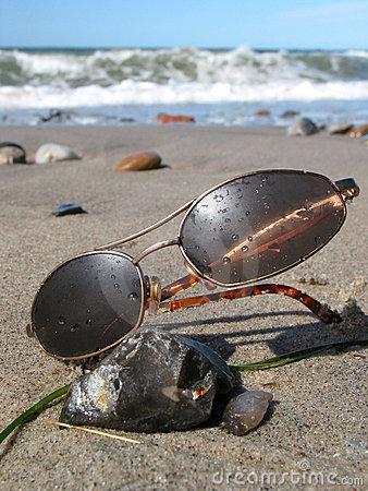 Wet sunglasses on the beach