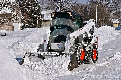 Bobcat skid steer removing snow from driveway
