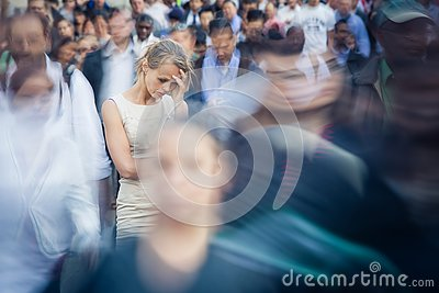 Depressed young woman feeling alone amid a crowd of people