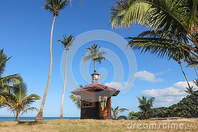 Cottage on the coconut beach. The clock tower or lifeguard tower , Hut against the blue sky