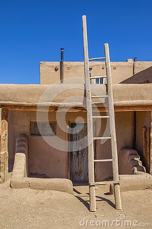 Ladder leading to second story apartments on traditional mud adobe pueblo with porch and old grunge wooden door in American