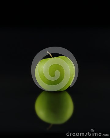 Artistic green Granny Smith apple close-up with reflection on black background