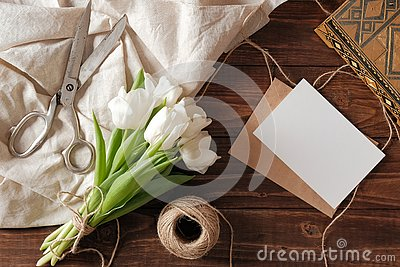 Spring bouquet of white tulip flowers, kraft envelope with blank card, scissors, twine on rustic wooden table. Wedding day composi