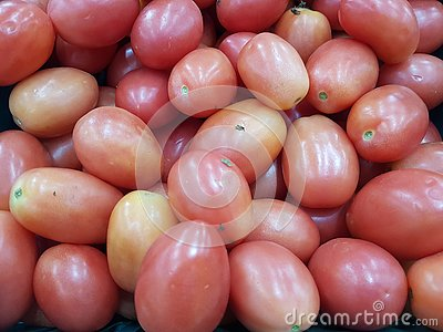 ittle tomatoes on a shelf at the market for sale usable for background
