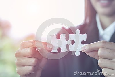 Business woman is trying to connect couple puzzle piece. Symbol of association and connection. Concept of business strategy