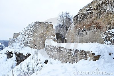 Ancient fortress wall and tower covered with snow, the wall is made of stone and limestone
