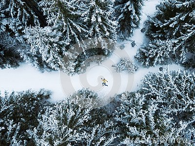 Aerial view of the lying man in winter forest