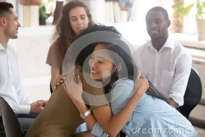 stock image of asian and african women embracing giving psychological support during therapy