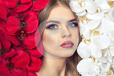 Portrait of a woman with beautiful make-up holds a white and red orchid in his hands.