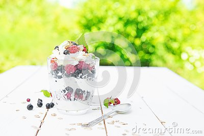 Healthy breakfast: layered dessrt yogurt parfait with fresh raspberries and black currant on wooden table over garden