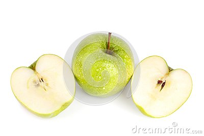 stock image of one whole big green apple and apple cut in two halves in water drops on white background isolated close up macro top view