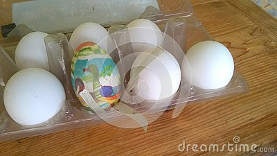 stock image of a closeup photograph of a single painted plastic easter egg nested inside of a plastic egg carton with several real chicken eggs