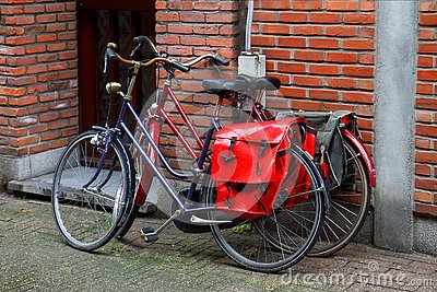 stock image of bicycles with red bags on the trunk.