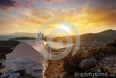 Sunset over the Greek island of Ios with a orthodox church in front on the Cyclades, Greece