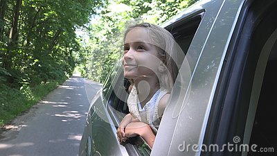 stock image of child traveling by car, kid face looking out the window, girl admiring nature