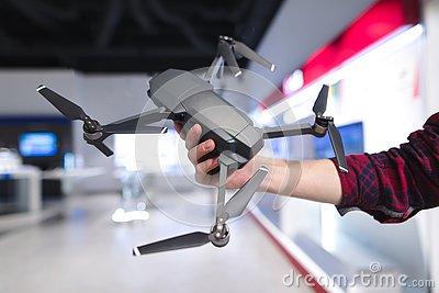 man`s hand holds a quadcopter in the background of a electronics store. Purchase a dron in a hardware store
