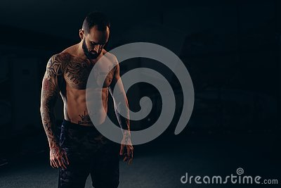 Shirtless concentrated male athlete looking to the floor