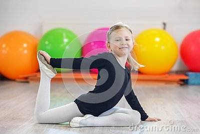 stock image of cheerful preschooler girl doing gymnastics in the gym. the concept of sports, education, hobbies, training and dance