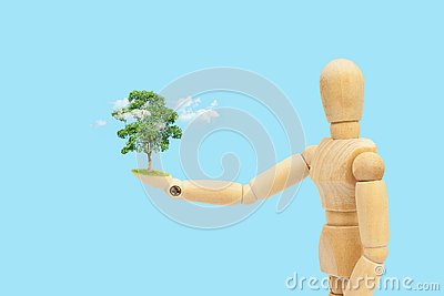 Wooden figure mannequin holding green tree and white cloud in hand.
