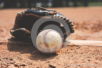 Baseball on field with glove close up in dirt.