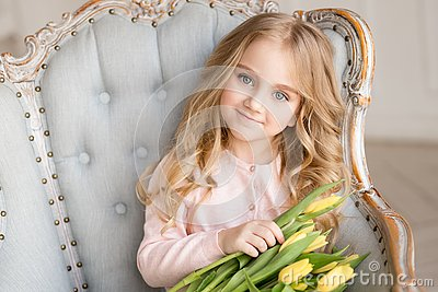 Beautiful pretty girl with yellow flowers tulips sitting in arm-chair, smiling. Indoor photo
