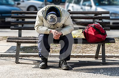 Homeless man, Poor homeless man or refugee sleeping on the wooden bench on the urban street in the city with bags of clothes and j