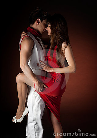 Young couple dancing passion on dark red light