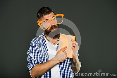 Calling attention to his manual. Book nerd wearing fancy glasses. Bearded man in party glasses with lesson book. Study