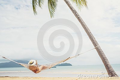Asian women relaxing in hammock summer holiday on beach