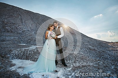 Fashionable and beautiful couple, happy blonde model girl with stylish hairstyle, in a white lace dress and stylish