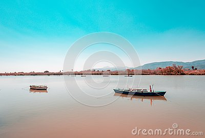 Calm lake with two fishing boats. Fresh water lagoon in Estany de cullera. Valencia, Spain