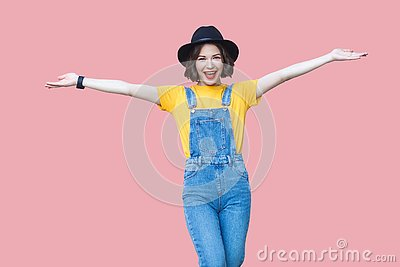 Portrait of excited beautiful young woman in yellow t-shirt, blue denim overalls, makeup, black hat standing with raised arms and