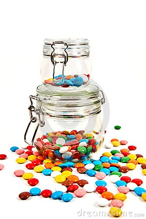 stock image of colorful candies in glass jar scattered isolated on white