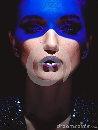 Portrait of fashion girl with stylish makeup and blue neon light on her face on the black background in the studio