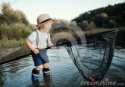 A small toddler boy standing in water and holding a net by a lake, fishing.