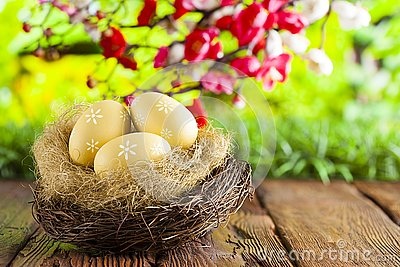 Three painted Easter eggs in the nest on table and nature background