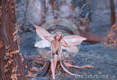 Charming fairy woke up in forest, sweetly smacks after sleeping, cue girl with blond hair, eyes closed in long green