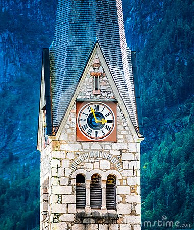 Closup view of protestant church`s clock on high tower in Hallstatt, Austria