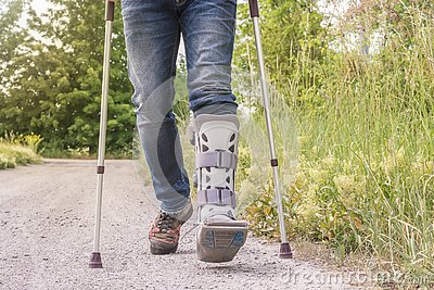 stock image of man is running with an orthosis and walking aids on a dirt road