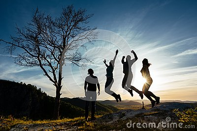 Friends have fun at sunset. Funny friends. A group of people in nature. Silhouettes of friends. Best friend. Friends traveling.