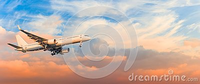 Passenger airplane is landing approach gear released, against sunset sky clouds, panorama. Travel aviation, flight, trip