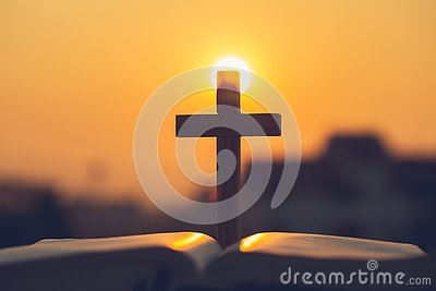 Silhouette of the cross on the holy bible, religion symbol in light and landscape over a sunrise, background, religious, faith