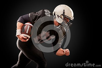 American football player in dark uniform with the ball is preparing to attack on a black background.